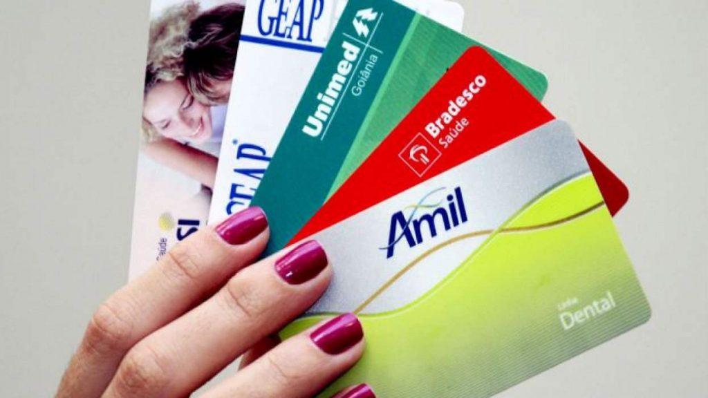 Mão segurando carteira de planos de saúde de várias operadoras